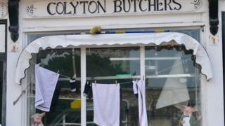 Washing hung up outside a butcher's shop in Colyton
