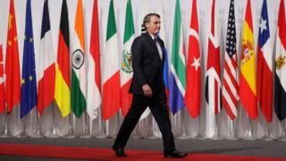 Bolsonaro caminha em frente a bandeiras em reunião do G20