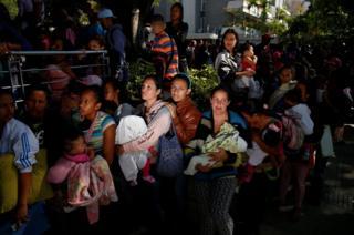 Mujeres con sus bebés haciendo una larga fila en Caracas.