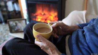 Pensioner drinking a cup of tea near an electric fire
