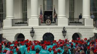 People in blue T-shirts and red MAGA caps gather outside the White House (10 Oct)