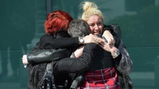Family members of victims show their reactions as they emerge from court