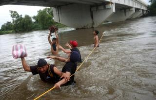 Men cross the Suchiate River with the help of rope to avoid the border checkpoint in Ciudad Hidalgo