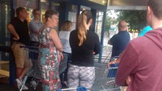 Shoppers queue outside supermarket Lidl for prosecco