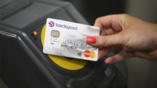 A credit card is tapped on a ticket gate terminal