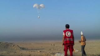 A worker from WFP's partner, the Syrian Arab Red Crescent, prepares to collect air-dropped cargo outside Deir al-Zour