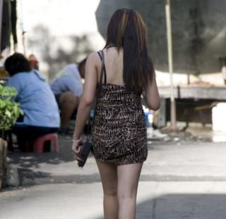 This picture shows a prostitute strolling in side street in a red light district, Bangkok, Thailand