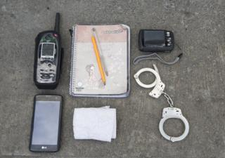 Sgt Lopez's phones, notepads and handcuffs are laid out on a table