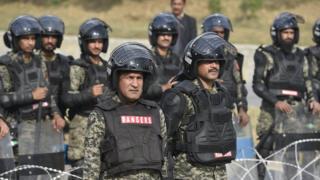 """Soldados paramilitares paquistaníes se posicionan cerca de seguidores del grupo religioso """"Tehrik Labayk Ya Rasool Allah (TLYRA)"""" durante una protesta en Islamabad, a fines de noviembre."""