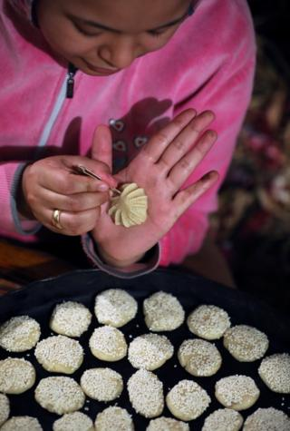A woman uses a pin-like implement to make decorative pattern on a small pastry before it goes in an oven.