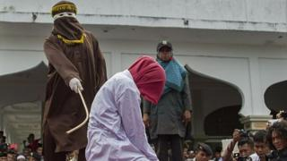 An Acehnese woman is lashed by a hooded local government officer during a public caning at a square in Aceh province, on June 12, 2015.