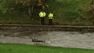 Two police officers stand on the bank of the River Kent with the top of a car visible in the water
