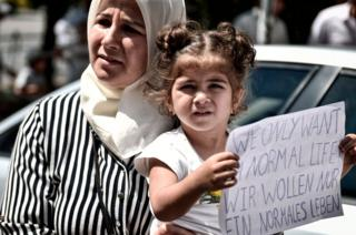 A Syrian girl holds a placard reading in English and German 'We only want a normal life' outside the German embassy in Athens on July 19, 2017.