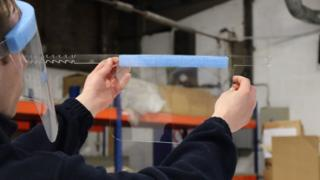 science ICL worker checks a visor during production process