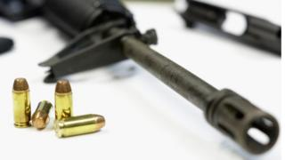 Four bullets beside the barrel of a rifle resting on a table