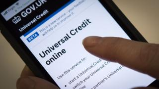 hand holding phone applying for universal credit online