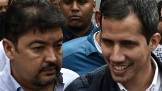 Venezuelan opposition leader and self-declared acting president Juan Guaido (R), greets supporters, next to his Chief of Staff Roberto Marrero