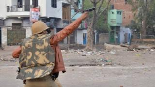 A police officer aims his gun towards protesters during demonstrations against India's new citizenship law in in Kanpur