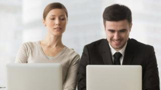 Mulher espiando conversa de homem em computador