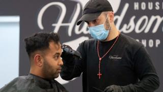 sports A barber wearing a face mask cuts a customer's hair in Wellington, New Zealand