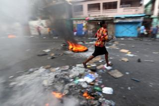 A woman walks past a burning barricade during anti-government protests in Port-au-Prince