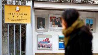 A person walks past while watching photographs outside the compound of the North Korean embassy in Berlin, Germany, 1 December 2017.