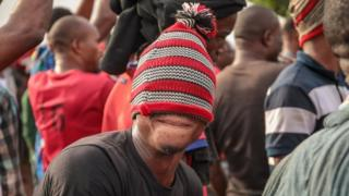 Man with a read woollen hat pulled over his eyes in Arondizuogu during the Ikeji Festival in Nigeria