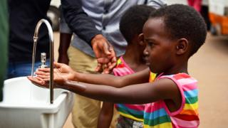 in_pictures A girls washing her hands at a public sink in Kigali, Rwanda - Wednesday 11 March 2020