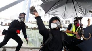 Pengunjuk rasaa melempar batu ke jembatan saat protes anti-pemerintah di dekat City University pada hari Selasa.