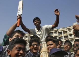 Schoolboy Pranav Dhanawade, 15, (C) is lifted by children as they celebrate during an inter-school cricket tournament in Mumbai, India, January 5, 2016.
