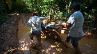 Two men are pushing a motorbike through the mud