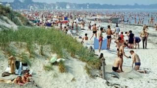 Holiday-makers (members of East Germany's Free German Trade Union Federation) on the beach in Warnemünde on the Baltic Sea (Photo by Harald Lange/ullstein bild via Getty Images) 14 августа 1969