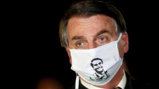 President Jair Bolsonaro speaks with journalists while wearing a protective face mask as he arrives at Alvorada Palace, amid the coronavirus disease (COVID-19) outbreak, in Brasilia, Brazil, May 22, 2020