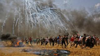 イスラエル軍が撃ち込んだ催涙ガス弾から逃げるパレスチナ人たち(14日、ガザ地区)