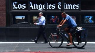 People make their way past the Los Angeles Times office building in downtown Los Angeles, California on July 16, 2018