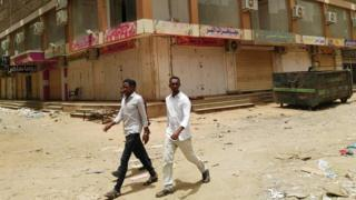 A group of men walk past a row of closed up shops in Khartoum's twin city, Omdurman