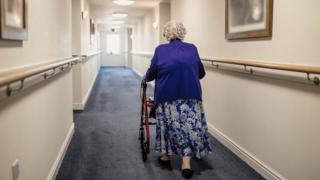 Stock image of a woman in a care home corridor