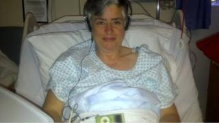 Researcher in hospital bed listening to music on headphones after surgery