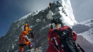 Кычкылтек баллондору менен альпинисттер Эвересттин чокусуна чыгып бара жатат.