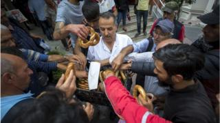 Imam Osman Gokrem (C) offers bagels to homeless people at the historic Selime Hatun Mosque a small Muslim house of worship dating back to the 17th century at the center of a populous Beyoglu district