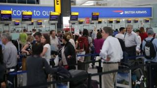 People queuing at check in at Heathrow Airport