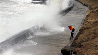 женщина сражается с зонтиком на набережной