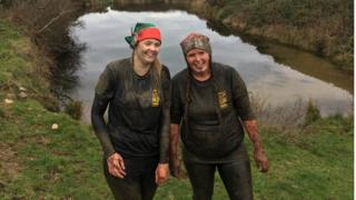 Photo of two mud-drenched women competitors