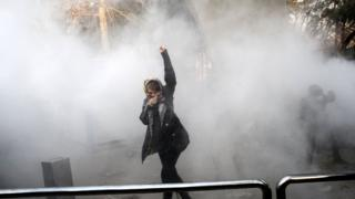 Iranian woman raises her fist amid tear gas at the University of Tehran during a protest in the capital on December 30, 2017