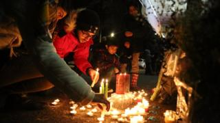 Mourners light candles and place flowers as they attend a vigil for the victims of a plane crash in Iran
