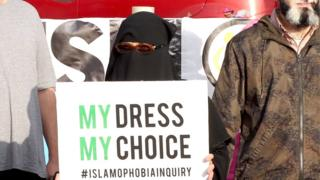 A woman wearing a burka protests near Mr Johnson's constituency office