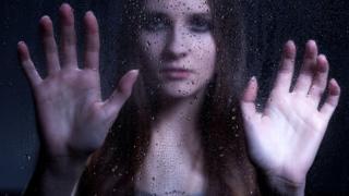 Женщина за стеклом с каплями