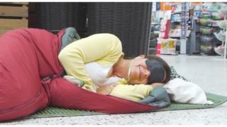 Woman sleeping on the supermarket floor wearing eye mask and earphones