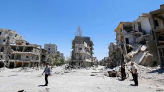 """People inspect a site hit by what activists said were barrel bombs dropped by forces loyal to Syria""""s President Bashar al-Assad in Aleppo""""s eastern district of Tariq al-Bab June 25, 2014."""