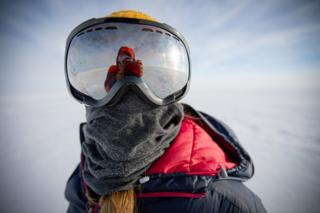 Person wearing a large pair of goggles - in icy Antarctic landscape... also a warm coat and scarf